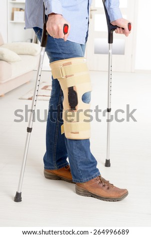 Man with leg in knee cages and crutches for stabilization and support  - stock photo