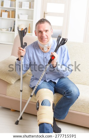 Man with leg in neck brace, knee cages and crutches for stabilization and getting up for rehabilitation - stock photo