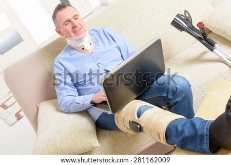 Man with leg in neck brace, knee cages and crutches for stabilization and support resting on a sofa with laptop.  - stock photo