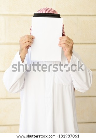 Man with long beard posing with empty copy space paper on his face - stock photo