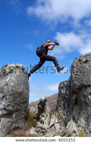 Man with long hair jumps from rock - low angle, against sky. Shot in Hottentots-Holland Mountains nature reserve, near Grabouw, Western Cape, South Africa.
