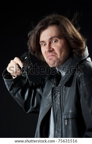 Man with long hair wearing leather jacket pointing a gun - stock photo