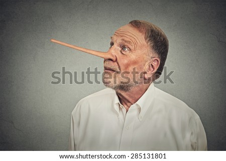 Man with long nose looking up avoiding eye contact isolated on grey wall background. Liar concept. Human face expressions, emotions, feelings. - stock photo