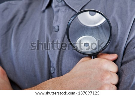 Man with magnifier on dark background - stock photo
