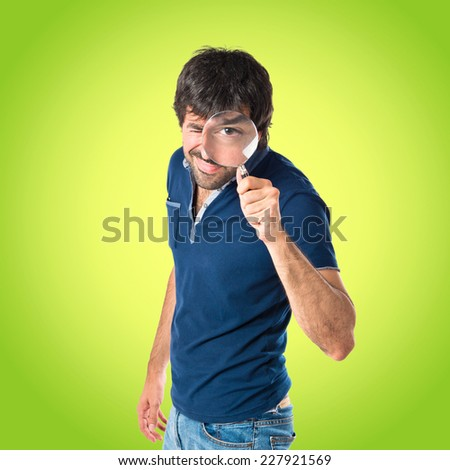 Man with magnifying glass over green background - stock photo