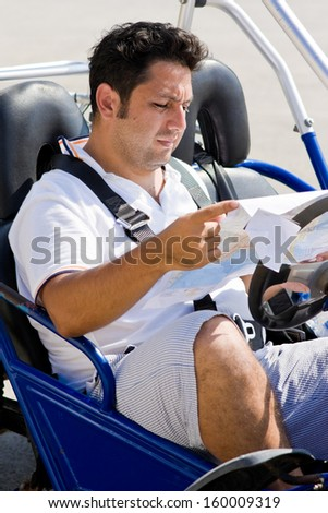 Man with map sits in buggy  - stock photo