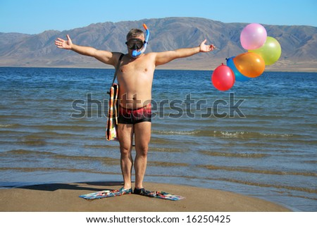 Man with mask, flippers and balloons is salutation  on the beach