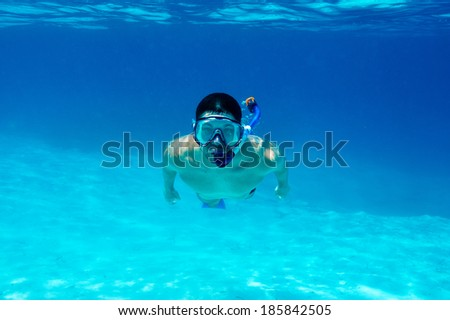 Man with mask snorkeling in clear water