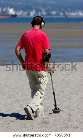 man with metal detector at the beach - stock photo
