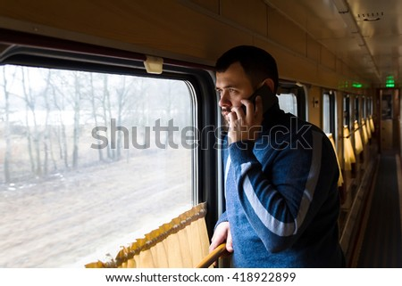 Man with mobile phone in hand in vintage train. Mixing styles. View from the window. - stock photo