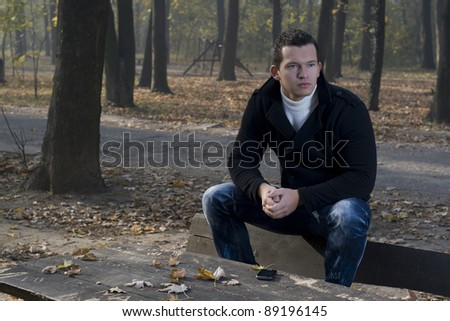 Man with mobile phone sitting on a park bench - stock photo