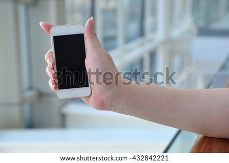 Man with modern mobile phone in hands touching on a blank screen.  - stock photo