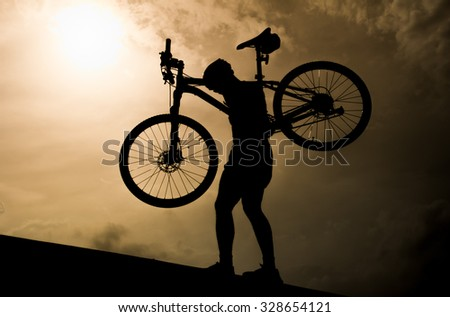 Man with mountain bicycle lifted above him  in the evening, Silhouette style. - stock photo
