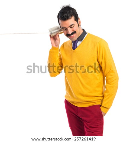 Man with moustache listening through a tin phone