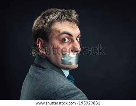 Man with mouth covered by masking tape - stock photo