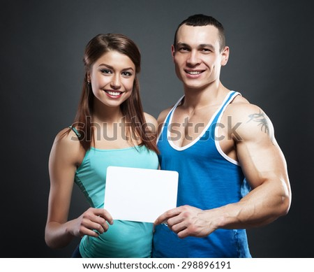 Man with muscular tattooed hand and woman holding blank notice board - stock photo