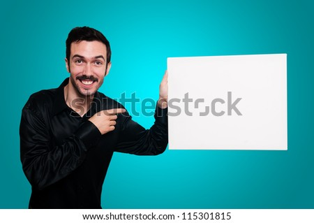 man with mustache and black jacket holding blank white board on blue background