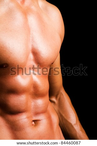 Man with naked muscled torso against black background - stock photo