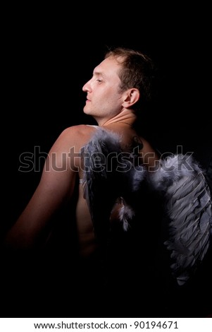 Man with naked torso and wings behind the back on a black background