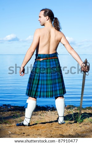 Man with naked torso in kilt on the sea background - stock photo