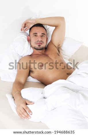 man with naked torso lying in bed - stock photo