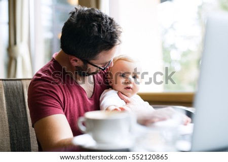 Man with notebook in cafe drinking coffee, holding his son