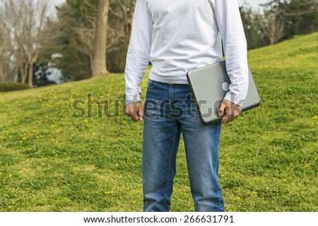 Man with notebook in park - stock photo