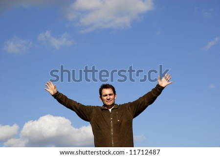 man with open arms and the blue sky - stock photo