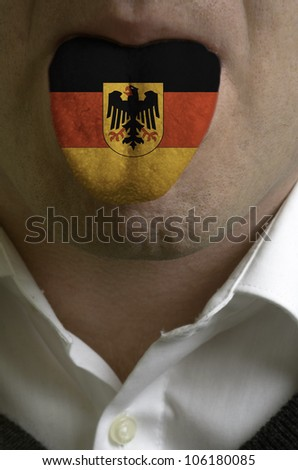 man with open mouth spreading tongue colored in germany flag as symbol of values like teaching, learning, multilingual speaking of different languages - stock photo