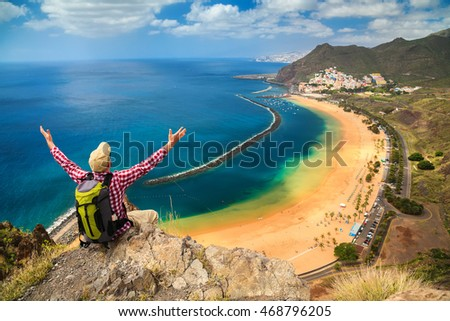 man with opened arms sitting on the edge of a cliff, enjoying amazing sea view of the beach near Santa Cruz de Tenerife - Playa de Las Teresitas, Canary Islands, Spain