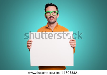 man with orange sweater holding blank white board on blue background