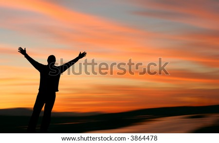 Man with outstretched arms facing a beautiful sunset. - stock photo