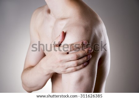 Man with pain in shoulder. Pain in the human body on a gray background - stock photo