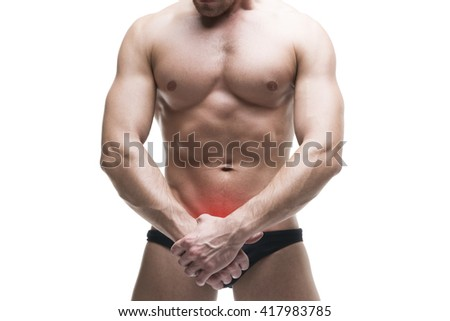 Man with pain in the prostate. Muscular male body. Handsome bodybuilder posing in studio. Isolated on white background with red dot