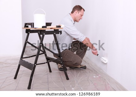 Man with paint roller kneeling - stock photo