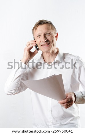 man with papers on the phone