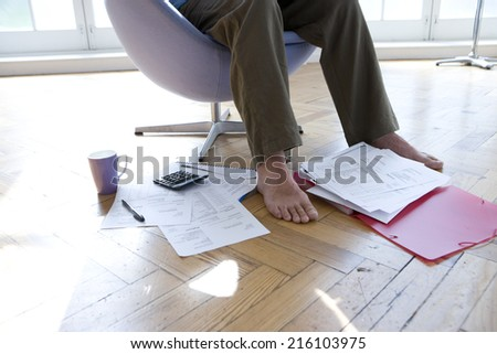 Man with paperwork by feet, in armchair, low section - stock photo