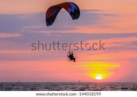 Man with para-glider flies in the sunset beach at Bangsaen,Thailand - stock photo
