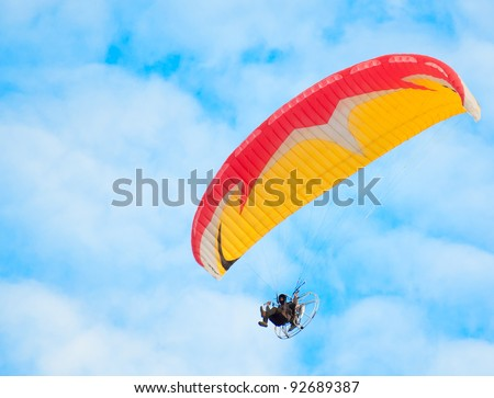 man with paraglider flies in the blue sky - stock photo