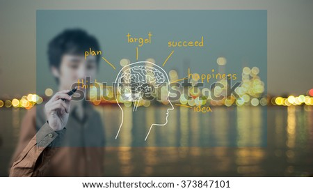 Man with pen drawing brain on whiteboard, Oil Refinery background - stock photo