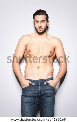Man with perfect torso. Handsome young muscular man with perfect torso standing against grey background - stock photo