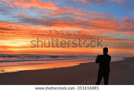 Man with phone on the beach at sunrise, Corolla,Outer Banks, North Carolina. - stock photo