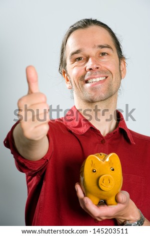 man with piggy bank and thumb up - stock photo