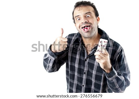 Man with pills in the tongue and hand . - stock photo