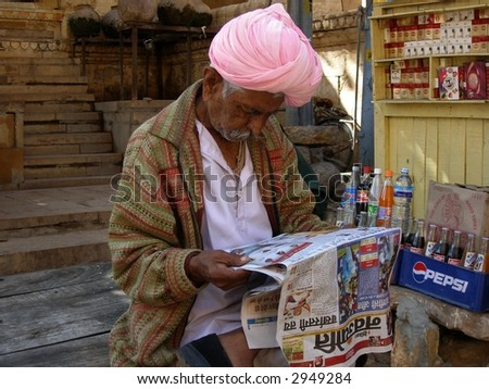 Man with pink turban reading newspaper - stock photo