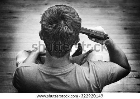 Man with pistol gun turned on his head wants to commit suicide, inside a house room. Black and white - stock photo