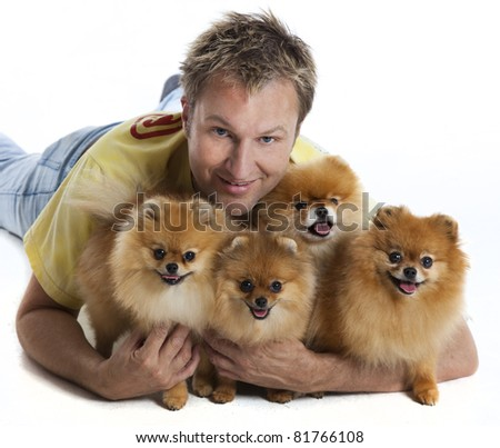 Man with 4 pomeranian dogs - stock photo