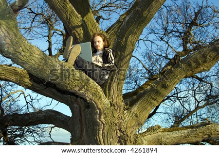 Man with portable computer at tree.