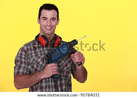 Man with power drill and earmuffs - stock photo