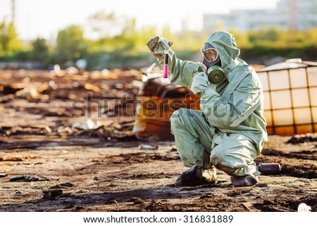 Man with protective mask and protective clothes explores danger area - stock photo